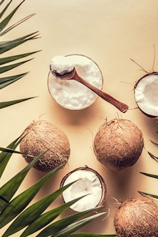Coconut oil and coconuts on a with tropical leaves.