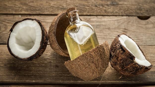 병에 든 코코넛 오일과 나무 배경에 있는 코코넛 헤어 케어 제품
