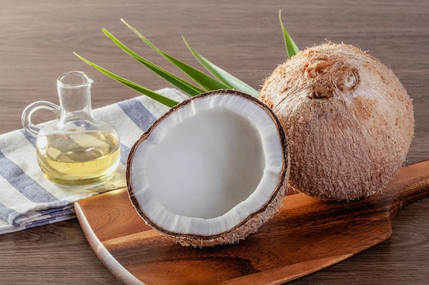 Кокосовое масло в бутылке с кокосовой стружкой и листьями зеленой пальмы на деревянном столе