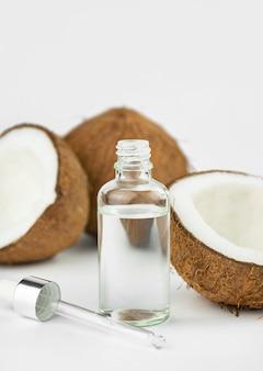 Кокосовое масло в бутылке с кокосами на белом столе. концепция ухода за кожей. уход за волосами и кожей.