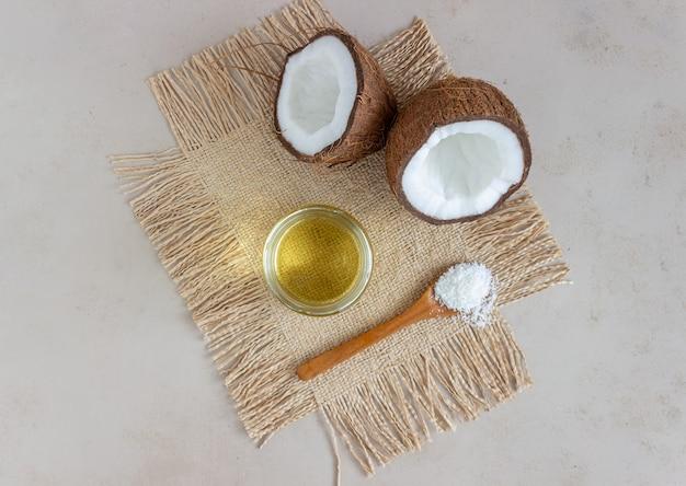 Кокосовое масло в банке и свежие кокосы на бежевой поверхности. натуральная косметика.