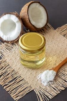 Кокосовое масло в банке и свежие кокосы на темной поверхности. натуральная косметика.