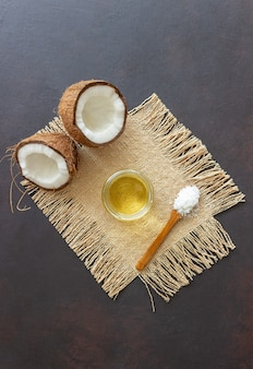 Coconut oil in a jar and fresh coconuts on a dark table. natural cosmetics.