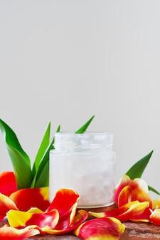 Coconut oil in a jar on white surrounded by tulip petals, close-up with copy space