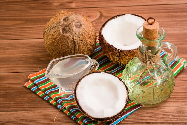 Coconut oil and milk and coconuts on a wooden table