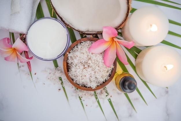 Кокосовое масло, тропические листья и свежие кокосы. кокосовые продукты спа на светлой деревянной поверхности.