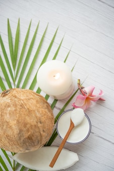 Coconut oil, tropical leaves and fresh coconuts. spa coconut products on light wooden surface.