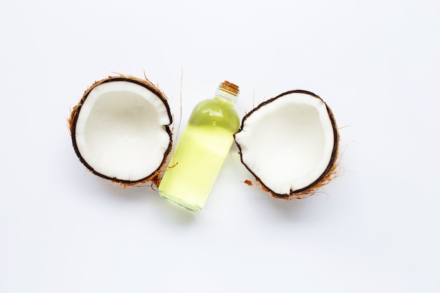 Coconut oil with coconuts on white