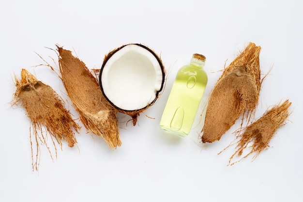 Coconut oil with coconuts on white.