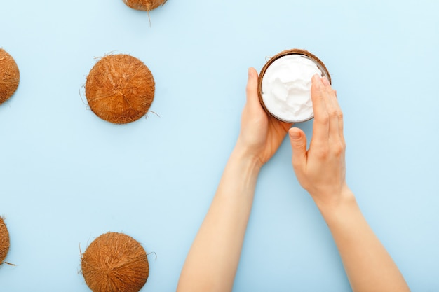 Coconut organic cosmetics, coconut cream, oil, lotion for skin or hair in female hands on pastel blue colored background. skin care moisturizing cream for soft skin. health and beauty concept.
