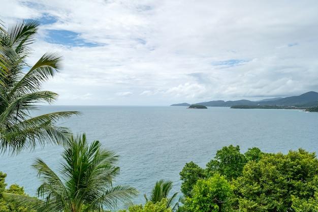 푸른 하늘과 열 대 바다 배경 코코넛 야자수 프레임 아름 다운 열 대 바다 여름 화창한 날 배경입니다.