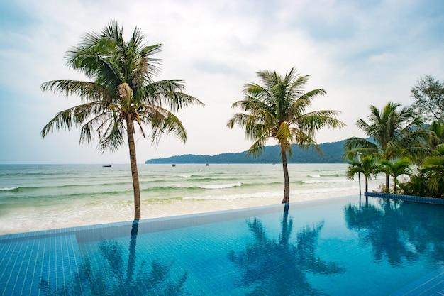 ココナッツのヤシが水に反射しています。海を背景にしたスイミングプール。熱帯の島での美しい贅沢な休日。美しい景色を望む屋外の屋外スイミングプール