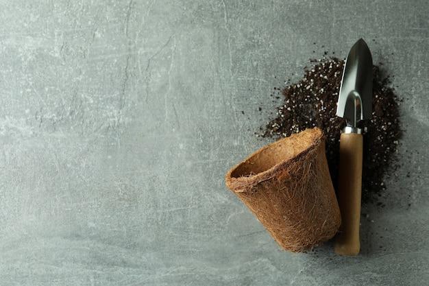 코코넛 냄비, 원예 삽 및 토양 회색 질감 배경