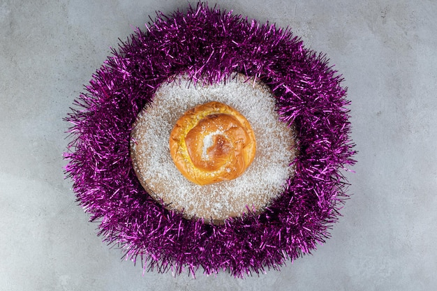 Coconut powder covered trivet with a bun in a garland circle on marble surface