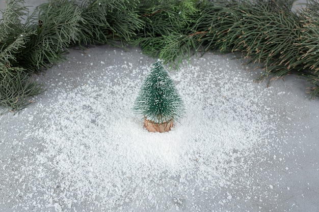 Coconut powder pile under tree figurine, in front of pine branches on marble surface