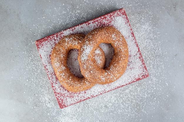 Polvere di cocco cosparsa di bagel su un libro su una superficie di marmo