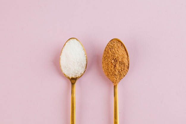 Coconut and refined white sugar in gold spoons on a pink surface
