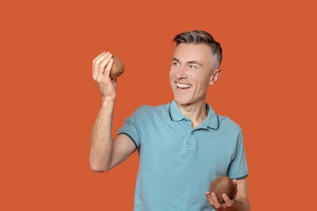 ココナッツ。オレンジ色の背景に手にココナッツナッツと夏のtシャツで若い大人の男を喜ばせる