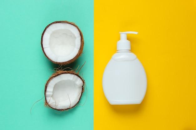 ココナッツシャンプー。シャンプーボトル、青黄色のパステルカラーの背景にココナッツの半分。ミニマルな美しさフラットレイ