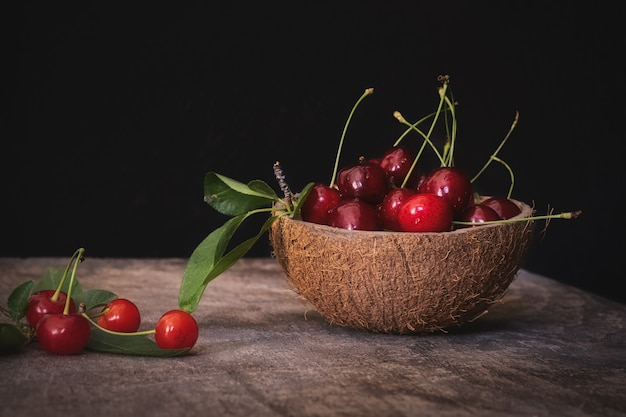 Coconut shell bowl full of fresh cherries in the shell on a wooden table on black wall
