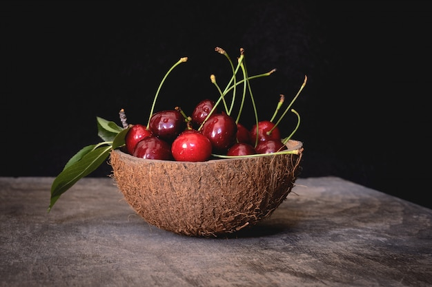 Coconut shell bowl full of fresh cherries in the shell on a wooden table on black