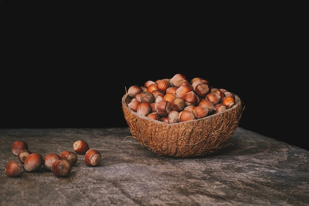 Coconut shell bowl full of hazelnuts in the shell on a wooden table on black wall