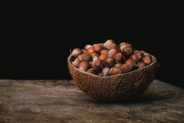 검은 벽에 나무 테이블에 껍질에 헤이즐넛의 전체 코코넛 껍질 그릇