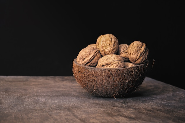 Coconut shell bowl full of walnuts in the shell on a wooden table on black wall