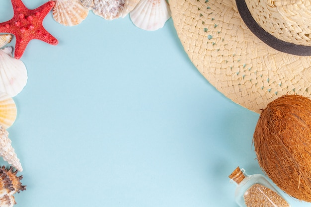 Coconut, starfish, shells, straw hat and bottle with sand on blue background