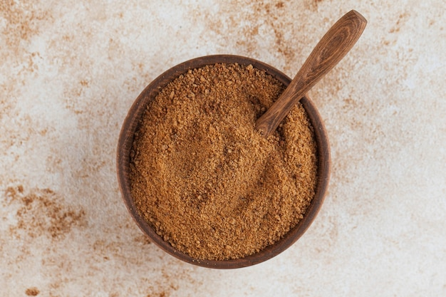 Coconut sugar in a wooden bowl with a palm leaf