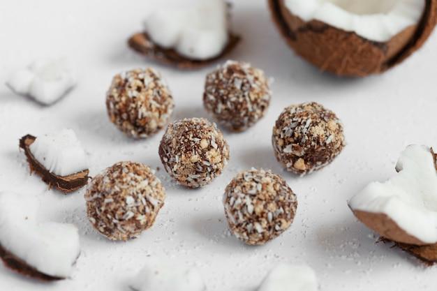 Кокосовые конфеты с шоколадом на светлом деревянном фоне. натуральные сладости без сахара.