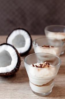 カフェでココナッツの柔らかいデザート。バレンタインデーのためのガラスのデザート。縦の写真。