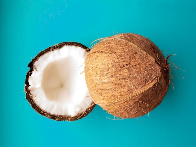 코코넛 나무 과일 코코넛은 파란색 배경에 분리된 두 개의 반으로 나뉩니다.