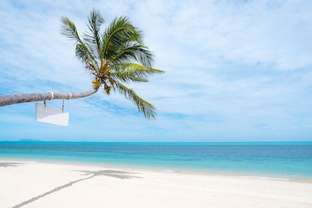 Coconut trees stretch into the sea with copy space.