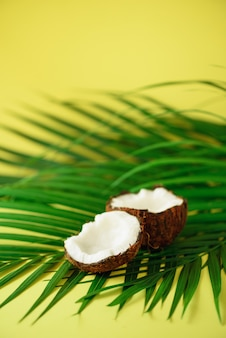 Coconut over tropical green palm leaves on yellow background. pop art design, creative summer concept. raw vegan food.