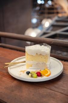 Кокосово-ванильный торт со взбитыми сливками и ягодами на тарелке в пекарне