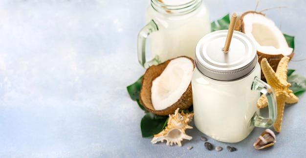 Кокосовый напиток или молоко в стеклянных банках здоровый летний тропический напиток