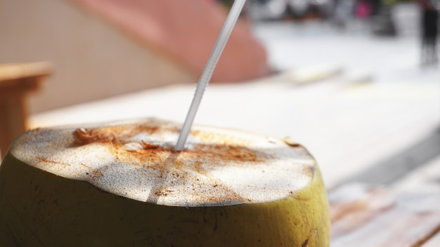 Coconut water drink on table with blurry background. beach cafe, travel and relax