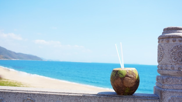 Coconut water drink on a tropical beach. sea beach in the background