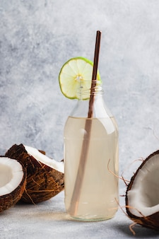 Coconut water in glass bottle with lime