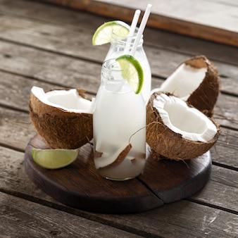Кокосовая вода в бутылках на деревянный стол. здоровый вегетарианский напиток