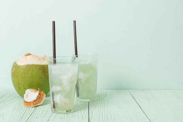 Кокосовая вода или кокосовый сок в стакане с кубиком льда