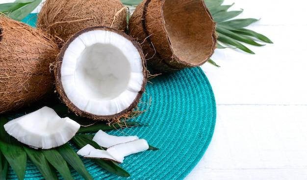 코코넛. 흰색 나무 테이블에 전체 코코넛, 껍질과 녹색 잎.