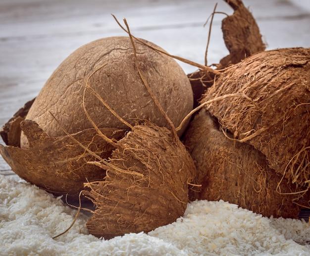 Noci di cocco intere trucioli sparsi sul tavolo di legno