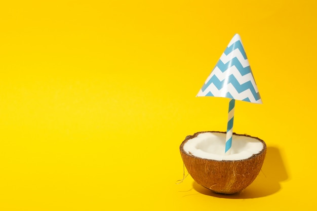 Coconut with beach umbrella on yellow, space for text