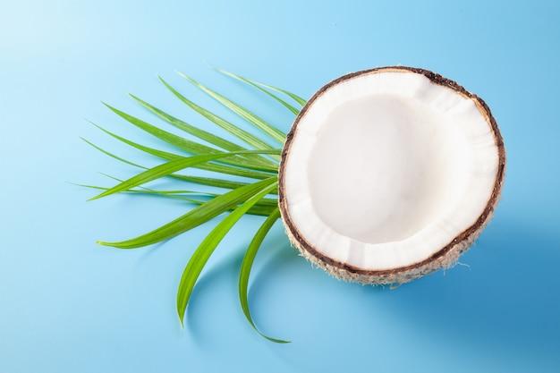 Кокос с кокосовым молоком на синем фоне