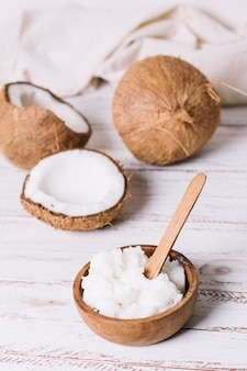 Cocco con scodella di olio di cocco