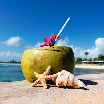 Noce di cocco con cannuccia in spiaggia al mar dei caraibi