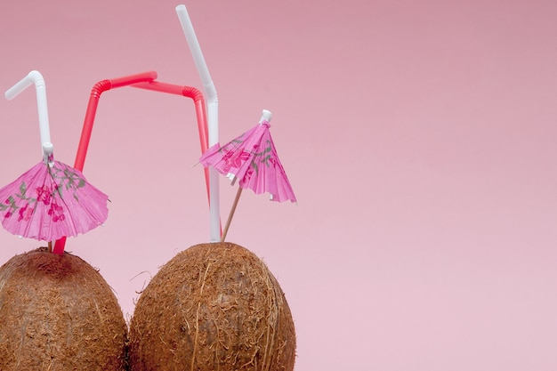 Coconut with drinking straw and umbrella on pink background