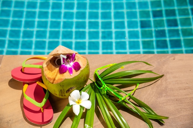 Coconut with festive decoration on side of swimming pool